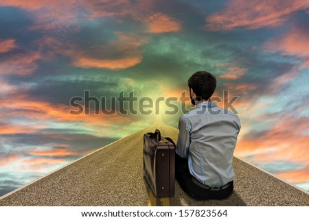 Businessman sitting and looking far to the road of future at sunset - stock photo