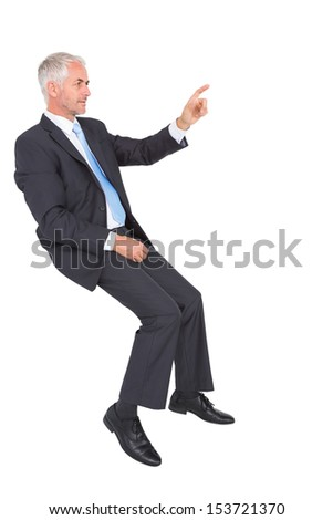 Businessman sitting and pointing against white background