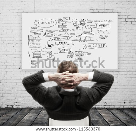 businessman sitting and scheme on wall - stock photo
