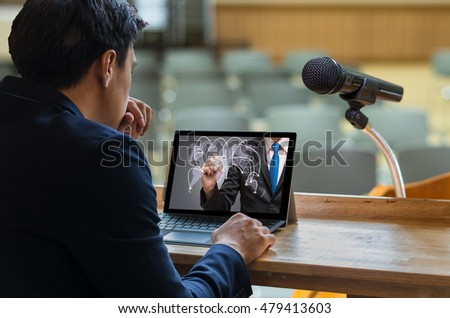 Businessman sitting and using computer laptop showing the connection on dark blue color over Microphone on the speech podium over the Abstract blurred photo of conference hall,Business meeting concept