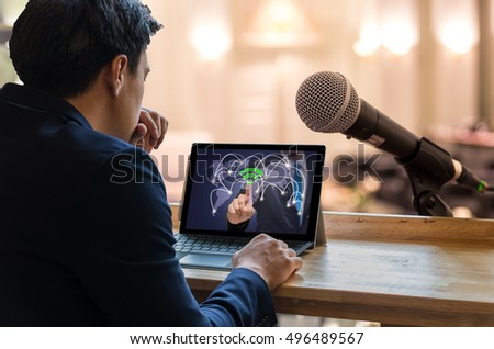 Businessman sitting and using computer laptop showing the wifi icon symbol on dark blue color background over the Microphone on the Abstract blurred photo of conference hall or seminar room background