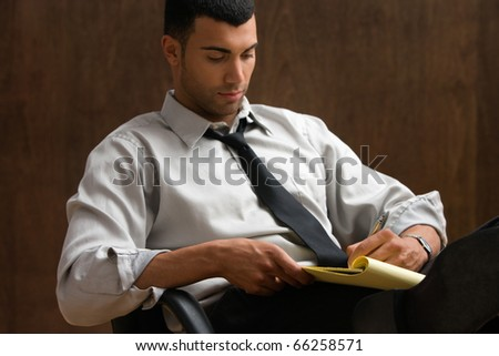 Businessman sitting and writing notes - stock photo