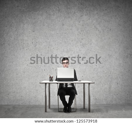Businessman sitting at a desk using a laptop - stock photo