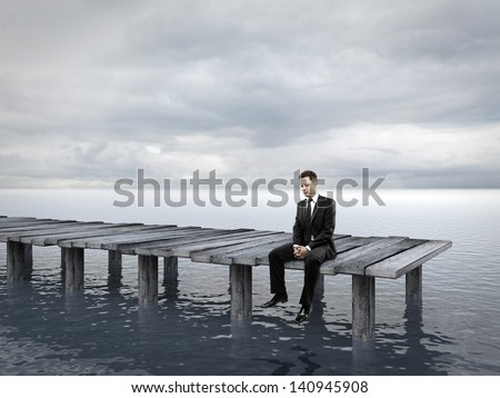 businessman sitting at a pier