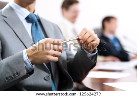 businessman sitting at a table and holding a pen