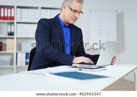Businessman sitting at a table in the office browsing the internet on a laptop with an engrossed expression, low angle view