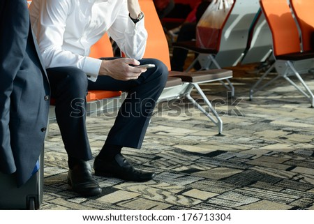 Businessman sitting at airport terminal using smartphone - stock photo