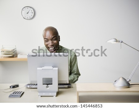 Businessman sitting at desk and laughing