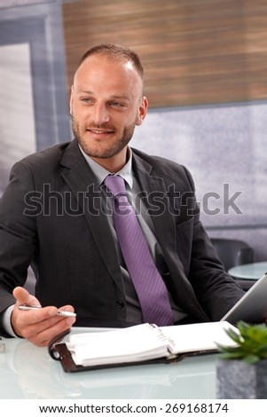 Businessman sitting at desk, holding pen, having personal organizer on desk, smiling, looking away.