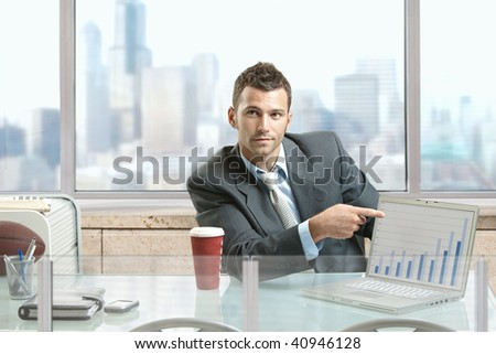 Businessman sitting at desk in office, pointing to charts on laptop computer screen.