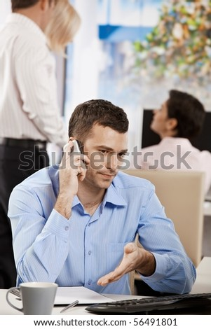 Businessman sitting at desk in office, talking on mobile phone. - stock photo