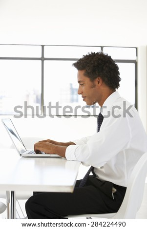 Businessman Sitting At Desk In Office Using Laptop - stock photo