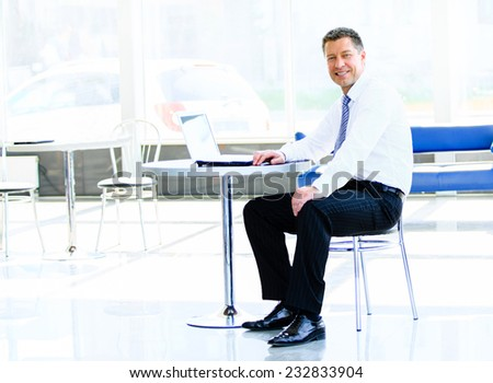 Businessman sitting at desk in office, working with laptop computer - stock photo