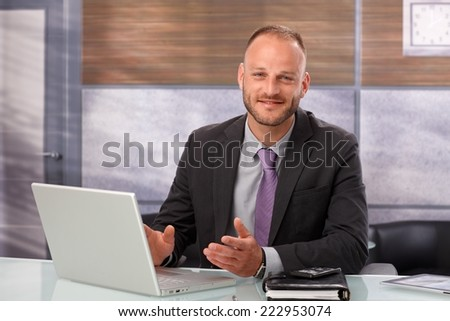 Businessman sitting at desk in office, working with laptop computer, smiling, looking at camera.