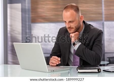 Businessman sitting at desk, working with laptop computer in office.