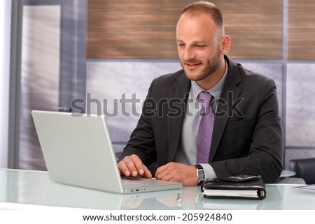 Businessman sitting at desk, working with laptop computer, smiling.