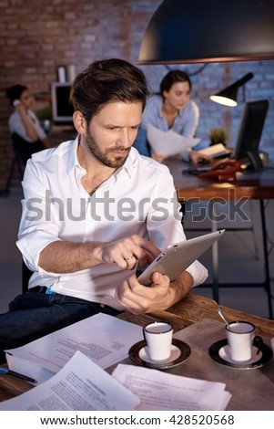 Businessman sitting at desk, working with tablet computer, concentrating. - stock photo