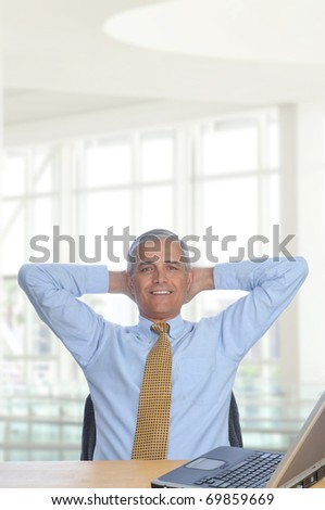 Businessman sitting at his desk in a modern office building with hands behind his head. Vertical Format - stock photo