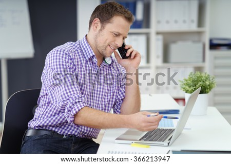 Businessman sitting at his desk in the office checking something on his laptop computer as he chats on the phone with a smile