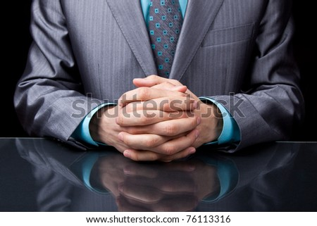 businessman sitting at his desk over black background - stock photo