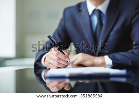 Businessman sitting at office desk and signing a contract - stock photo