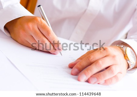 Businessman sitting at office desk signing a contract - shallow focus on signature - stock photo
