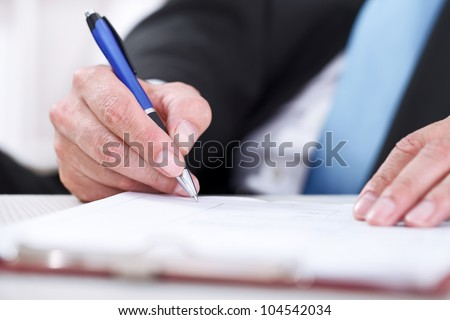 Businessman sitting at office desk signing a contract with focus on signature. - stock photo
