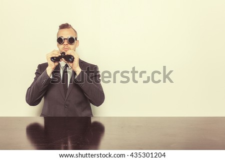 Businessman sitting at office desk with binoculars