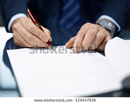 Businessman sitting at shiny office desk signing a contract with noble pen - stock photo