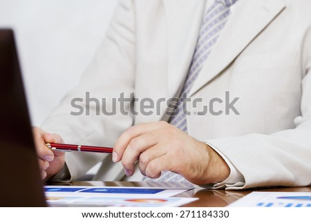 Businessman sitting at table and working in the office - stock photo