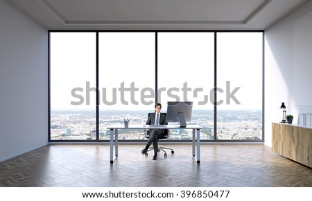 Businessman sitting at table in big office. Panoramic window behind. City view. Concept of work.