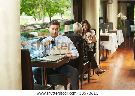 Businessman sitting at table in cafe, reading newspaper and drinking coffee. Young women talking in the background. - stock photo