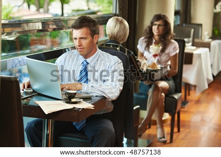 Businessman sitting at table in cafe using laptop computer. Young women having sweets in the background. - stock photo