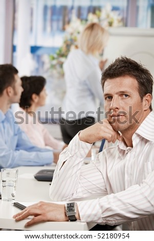 Businessman sitting at table in meeting room at office, looking at camera. - stock photo