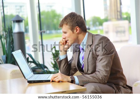 Businessman sitting at table in office hall, talking on mobile phone and using laptop computer - stock photo