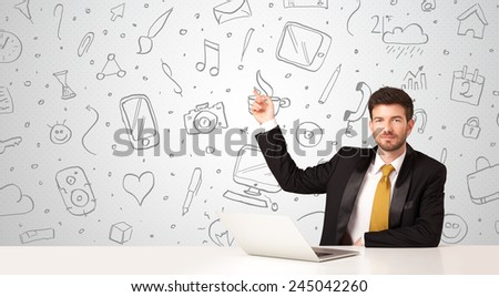 Businessman sitting at table with hand drawn media icons and symbols  - stock photo