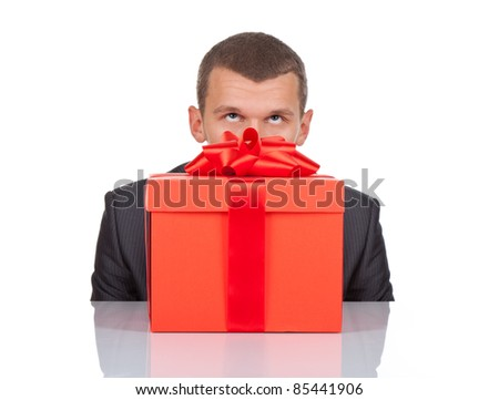Businessman sitting at the desk with gift box looking up isolated over white background, series photo - stock photo