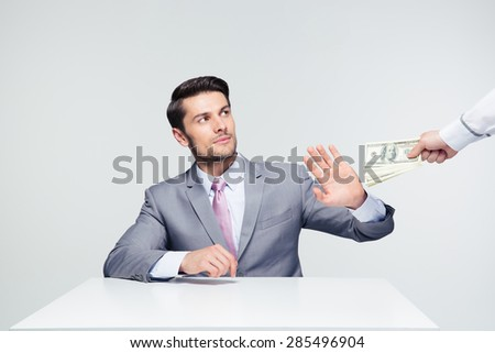 Businessman sitting at the table and gesturing stop sign while someone proposing money to him over gray background - stock photo