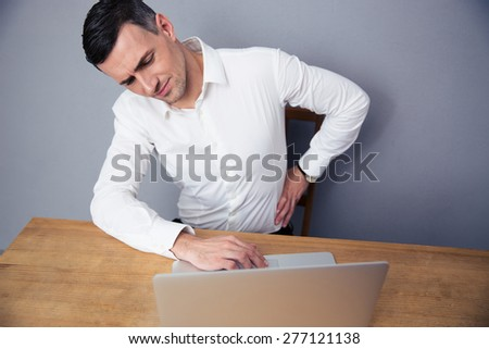 Businessman sitting at the table and having backache - stock photo