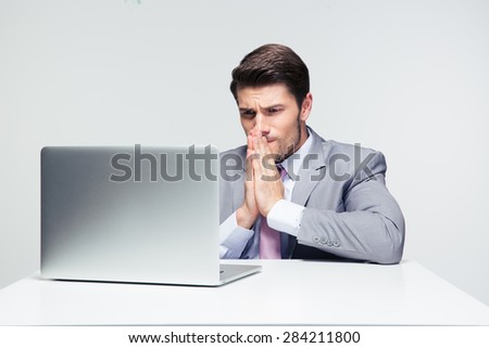 Businessman sitting at the table and praying over gray background