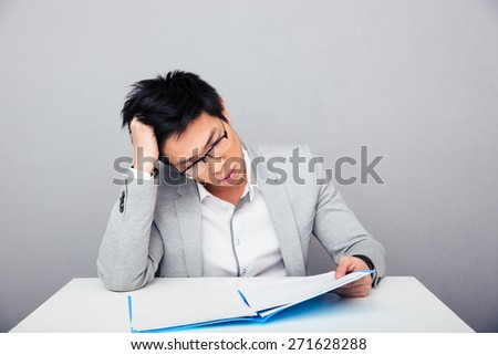 Businessman sitting at the table and reading papers in office - stock photo
