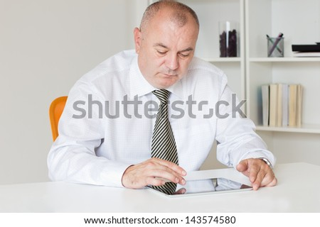 Businessman sitting at the table and working on a Digital tablet. - stock photo