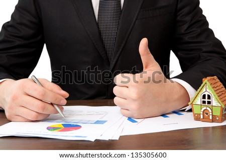 businessman sitting at the table with charts and a house and sign a contract - stock photo