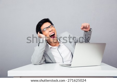 Businessman sitting at the table with laptop and yawning over gray background - stock photo