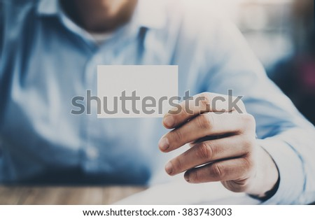 Businessman sitting at the wood table and showing a blank business card. Horizontal mockup