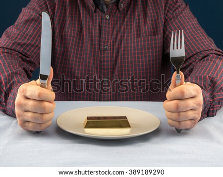 Businessman sitting behind a table with fork and knife ready to eat bar of gold served on plate - business concept - stock photo