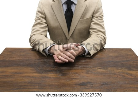 Businessman Sitting Behind the Table with Hands Clasped - Isolated