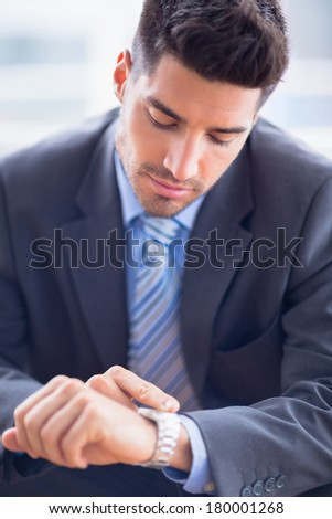 Businessman sitting checking his watch in the office