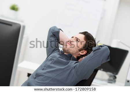 Businessman sitting daydreaming at his desk at the office leaning back in his chair looking up into the air with a pleased thoughtful smile and his hands clasped behind his head - stock photo