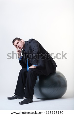 businessman sitting down on a gym fitness ball